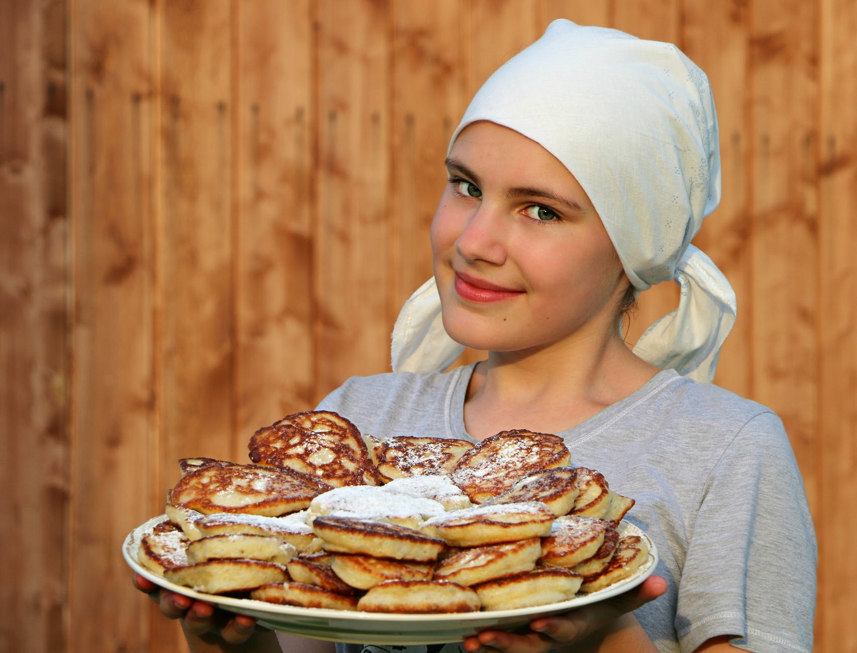woman in grey crew neck shirt holding a white ceramic plate with pancakes