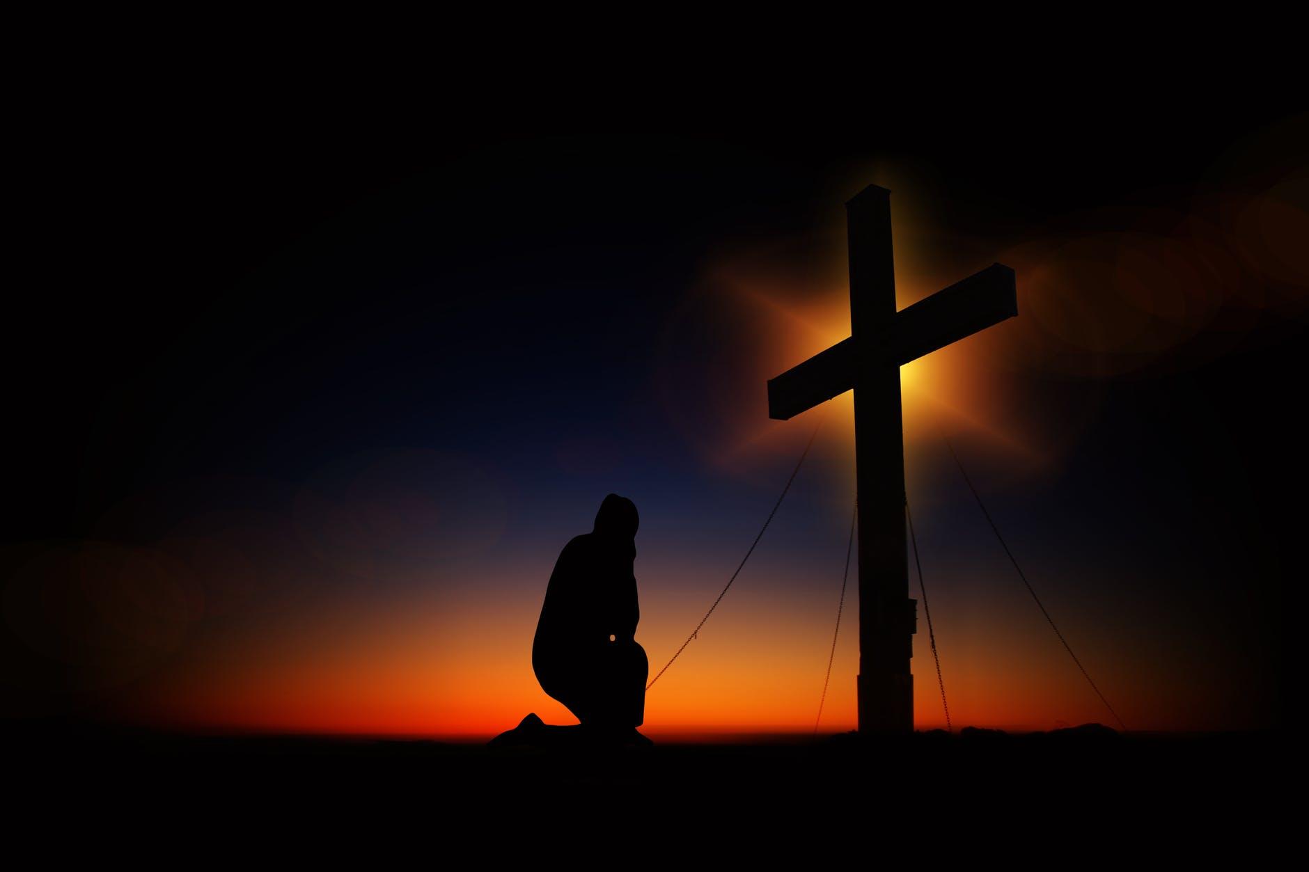 man kneeling in front of cross
