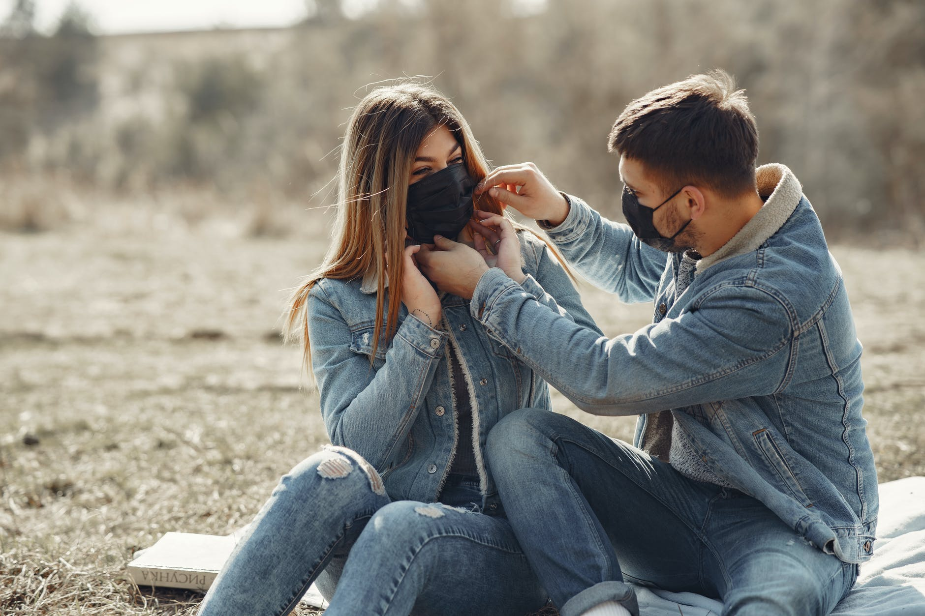 cheerful young couple in black medical masks resting on plaid on sunny meadow in countryside
